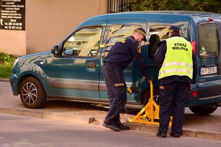 Varsovia, Polonia. 1 de octubre de 2018. Policía Municipal. Rueda de coche bloqueada por bloqueo de rueda. Violación de estacionamiento ilegal