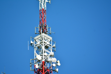Telecommunication mast with microwave link and TV transmitter antennas on blue sky. Stock Photo