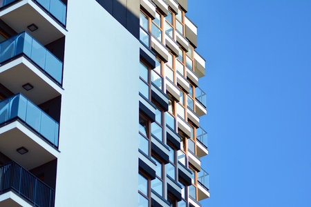 Fragment of a building with windows and balconies. Modern home with many flats.