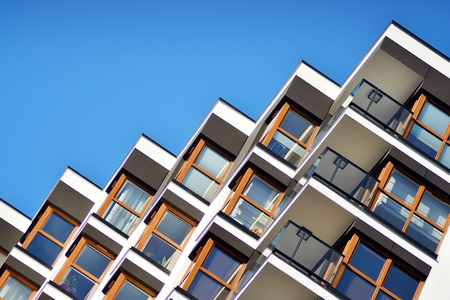 Fragment of a building with windows and balconies. Modern home with many flats. Stock Photo