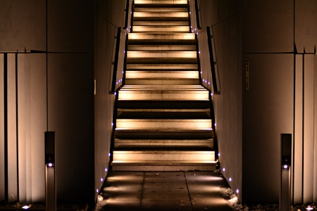 Illuminated apartment building staircase exhaling up to the entrance in the night city Stock Photo