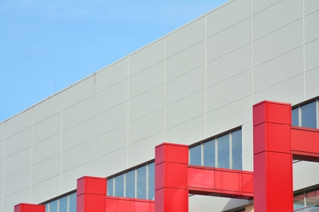 New office building in business center. Wall made of red steel and glass with blue sky.