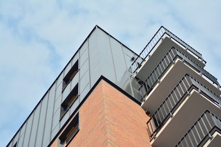 European modern residential architecture. Fragment of a modern apartment building in front. Very modern apartment house. Stock Photo