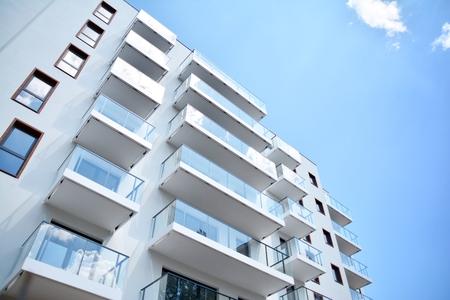 Moderne Wohnhäuser an einem sonnigen Tag mit einem blauen Himmel. Fassade eines modernen Wohnhauses Standard-Bild