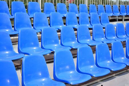 Empty blue plastic chairs in a row at the football stadium Stock Photo