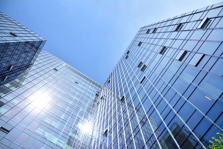 Bottom view of modern skyscrapers in business district against blue sky