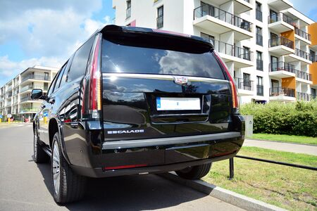 Warsaw, Poland. July 22, 2019. Motor car Cadillac Escalade at the city street. Cadillac Escalade SUV commands attention with its superior craftsmanship and iconic design. Imagens - 128668483