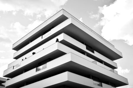 Modern multi-storey luxury housing concept. Modern apartment building with dark sky and clouds. Dark shades of gray.