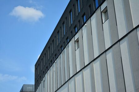 New office building in business center. Wall made of steel and glass with blue sky.