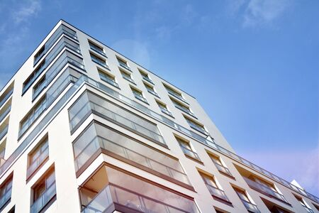 Modern apartment buildings on a sunny day with a blue sky. Facade of a modern apartment building.Glass surface with sunlight.
