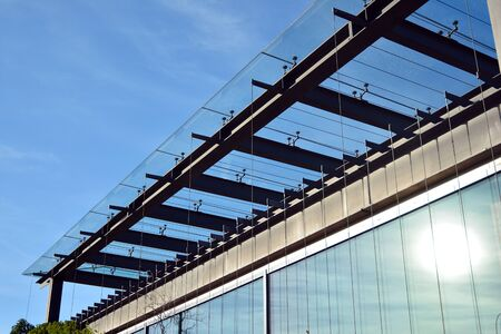 New office building in business center. Wall made of steel and glass with blue sky. Foto de archivo - 130815854