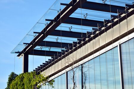 New office building in business center. Wall made of steel and glass with blue sky. Foto de archivo - 130815856
