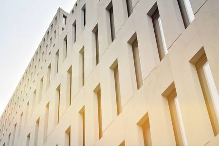Modern office building detail. Perspective view of geometric angular concrete windows on the facade of a modernist brutalist style building surface with sunlight.