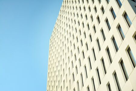 Modern office building detail. Perspective view of geometric angular concrete windows on the facade of a modernist brutalist style building.
