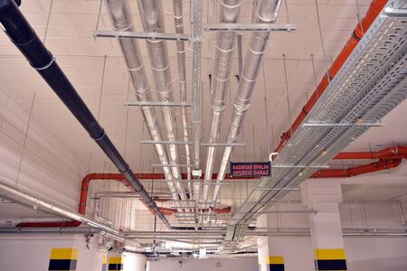 Water pipes and cable trays run under ceiling of a building
