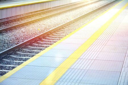 Fragment of the platform and railroad tracks in sunlight. Stock fotó