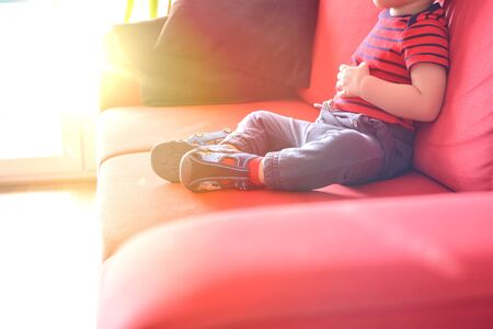 Child sitting on the sofa at home