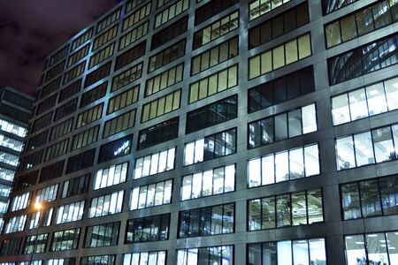 Pattern of office buildings windows illuminated at night. Lighting with Glass architecture facade design with reflection in urban city. Stock fotó - 133484821