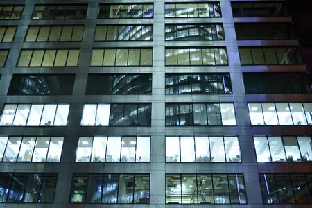 Pattern of office buildings windows illuminated at night. Lighting with Glass architecture facade design with reflection in urban city. Stock fotó - 133484822