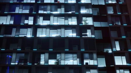 Pattern of office buildings windows illuminated at night. Lighting with Glass architecture facade design with reflection in urban city. Stock fotó - 133484848