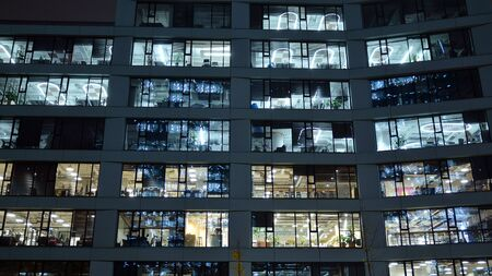 Pattern of office buildings windows illuminated at night. Lighting with Glass architecture facade design with reflection in urban city. Stock fotó - 133484847