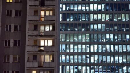 Pattern of office buildings windows illuminated at night adjacent to an old residential building. Lighting with Glass architecture facade design with reflection in urban city.