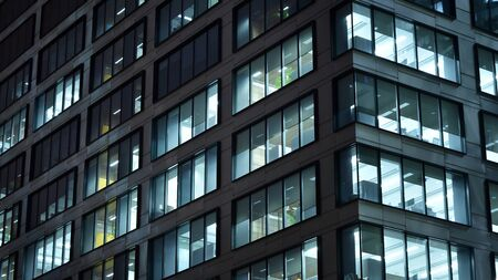 Pattern of office buildings windows illuminated at night. Lighting with Glass architecture facade design with reflection in urban city. Stock fotó - 133484880