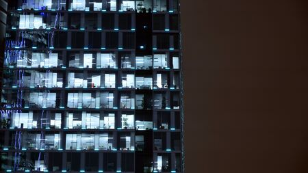 Pattern of office buildings windows illuminated at night. Lighting with Glass architecture facade design with reflection in urban city.
