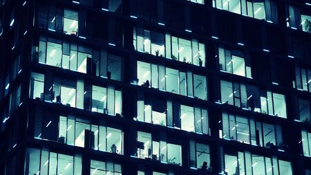 Pattern of office buildings windows illuminated at night. Lighting with Glass architecture facade design with reflection in urban city. Stock fotó - 133484903