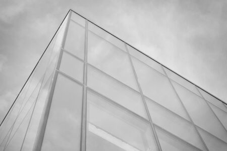 Curtain wall made of toned glass and steel constructions under sky. A fragment of a building. Black and white. Banco de Imagens