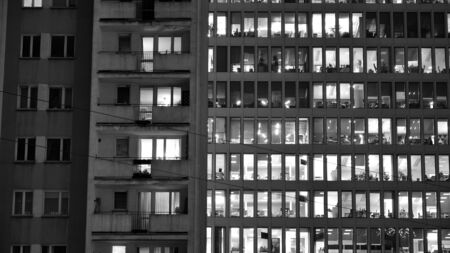 Pattern of office buildings windows illuminated at night adjacent to an old residential building. Lighting with Glass architecture facade design with reflection in urban city. Black and white.