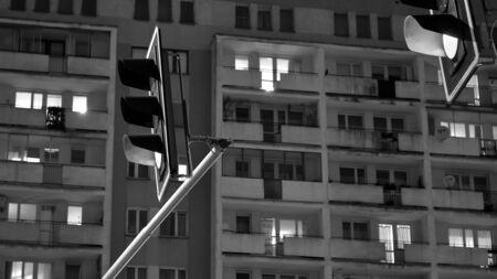 Exterior of apartment building at night with light from windows. Street lights on the background of the building. Black and white.