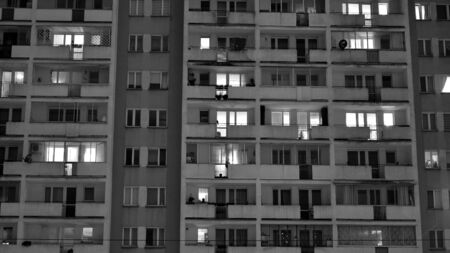 Exterior of apartment building at night with light from windows. Black and white.