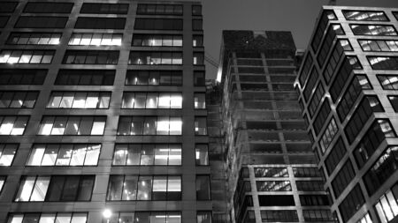 Pattern of office buildings windows illuminated at night. Lighting with Glass architecture facade design with reflection in urban city. Black and white.