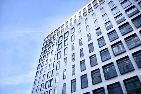 Modern European building. White building with many windows against the blue sky. Abstract architecture, fragment of modern urban geometry. Stock fotó - 133966786