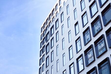 Modern European building. White building with many windows against the blue sky. Abstract architecture, fragment of modern urban geometry. Stock fotó - 133966785