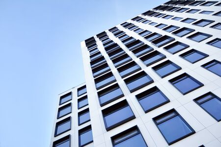 Modern European building. White building with many windows against the blue sky. Abstract architecture, fragment of modern urban geometry. Stock fotó - 133966788