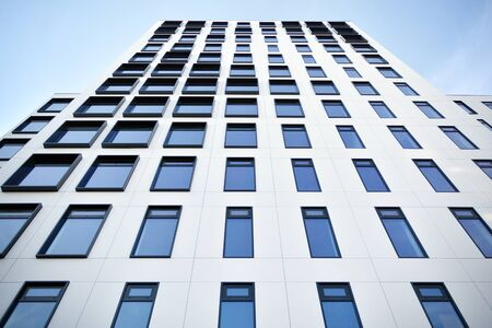 Modern European building. White building with many windows against the blue sky. Abstract architecture, fragment of modern urban geometry. Stock fotó - 133966792