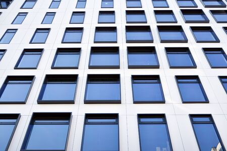Modern European building. White building with many windows against the blue sky. Abstract architecture, fragment of modern urban geometry. Stock fotó - 133966819