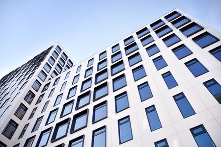 Modern European building. White building with many windows against the blue sky. Abstract architecture, fragment of modern urban geometry.