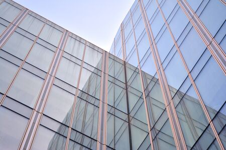 Modern office building wall made of steel and glass with blue sky Foto de archivo - 133966806
