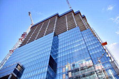 Nuevo y moderno rascacielos de oficinas que se está construyendo en una ciudad. Edificio de fachada arquitectónica durante la construcción con elementos de vidrio terminados y en hormigón.