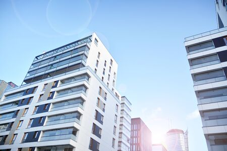 Modern apartment buildings on a sunny day with a blue sky. Facade of a modern apartment building. Glass surface with sunlight. Stock Photo