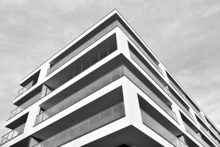 Effetti di luce dei raggi solari sugli edifici urbani. Frammento di appartamento residenziale moderno con esterno di edifici piani. Particolare di nuova casa di lusso e complesso domestico. Bianco e nero.