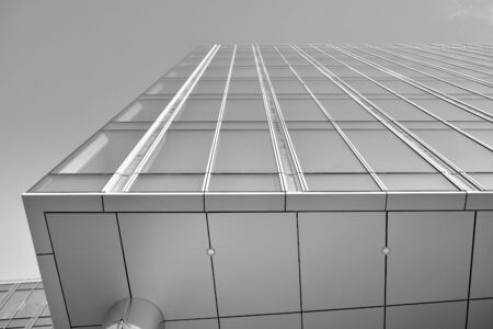 Sun rays light effects on urban buildings in sunset. Modern office building detail, glass surface with sunlight. Business background. Black and white. Stock fotó