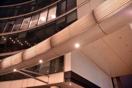 Night architecture - building with glass facade. Modern building in business district. Concept of economics, financial. Photo of commercial office building exterior. Abstract image of office building