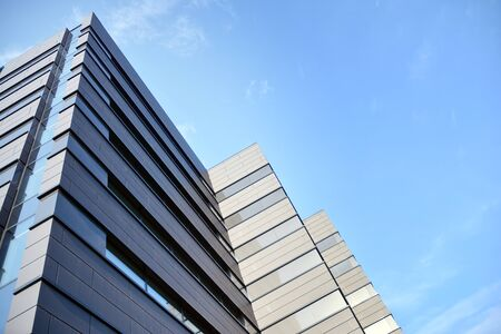A view at a straight facade of a modern building with a dark gray facade. Dark gray metallic panel facad. Modern architectural details.