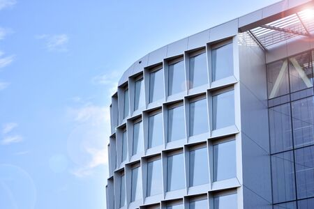 Modern architecture with sun ray. Glass facade on a bright sunny day with sunbeams in the blue sky.