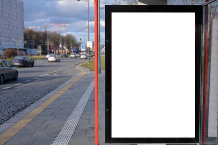 Vertical blank white billboard at bus stop on city street. In the background buildings and road. Stock Photo