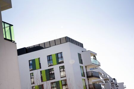 Exterior of new apartment buildings on a blue cloudy sky background. No people. Real estate business concept. Standard-Bild